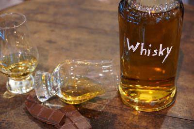 グラスに注がれたウイスキーとボトル