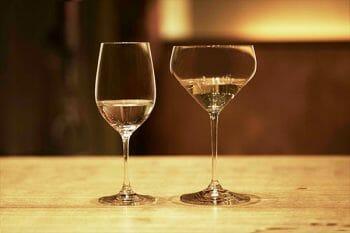 """左がリーデルの大吟醸グラス、右が""""純米""""グラス。純米グラスは横長でユニークな形をしている。"""